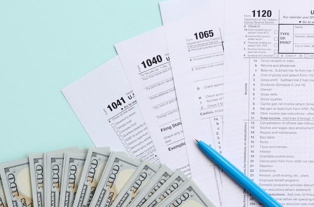 Steuerformulare liegen nahe hundert dollarscheinen und blauem stift auf einem hellblauen hintergrund. Premium Fotos