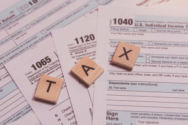 Steuern sie mit hölzernen alphabetblöcken, stift auf us-steuerformularhintergrund Premium Fotos