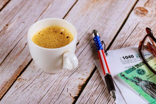 Steuersaison ein büro mit einer brille und stift auf einkommenssteuererklärung 1040 formular mit schwarzem kaffee Premium Fotos