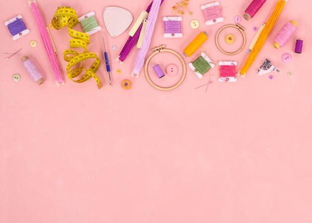 Stickerei und kreuzstichzubehör auf rosa hintergrund. flach liegen. kopieren sie platz. Premium Fotos
