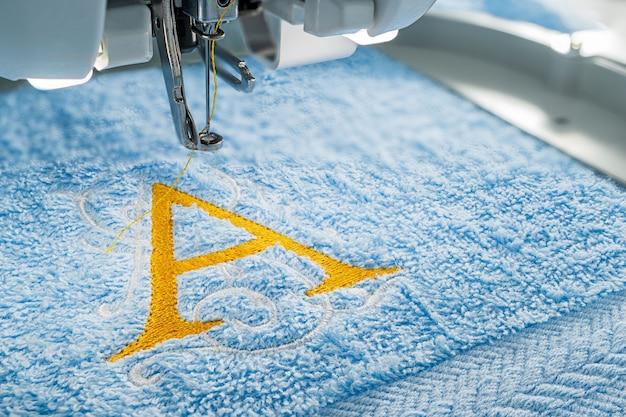 Stickmaschine und alphabet design auf handtuch Premium Fotos