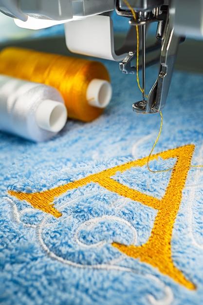 Stickmaschine und logo-design auf handtuch Premium Fotos