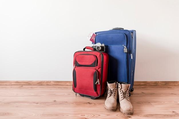 Stiefel in der nähe von koffern und kamera Kostenlose Fotos