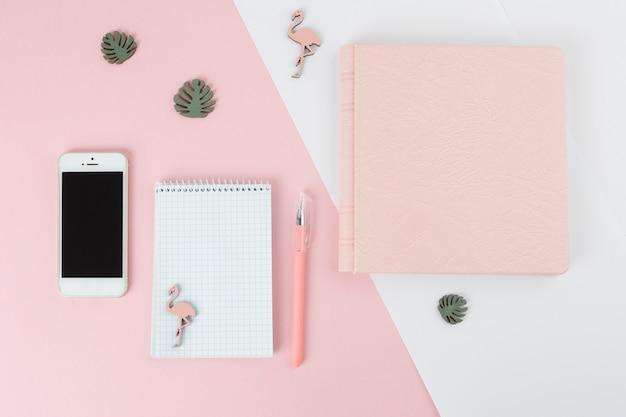 Stift in der nähe von notebook, smartphone, album und kleinen dekorationen Kostenlose Fotos