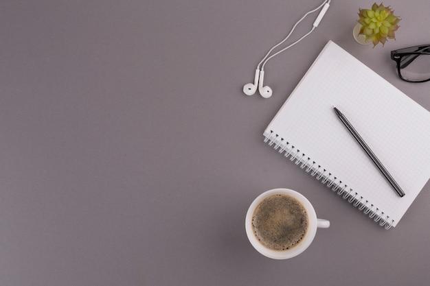 Stift in der nähe von notizblock, tasse, ohrhörer und brille Kostenlose Fotos