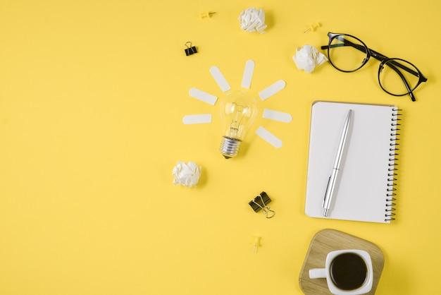 Stift, notizblock, brille, kaffeetasse und glühbirne auf gelbem grund. Premium Fotos