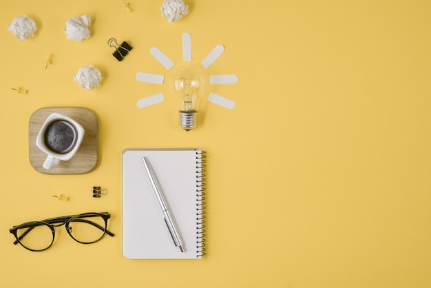 Stift, notizblock, brille, tasse kaffee, glühlampe auf gelbem grund. Premium Fotos