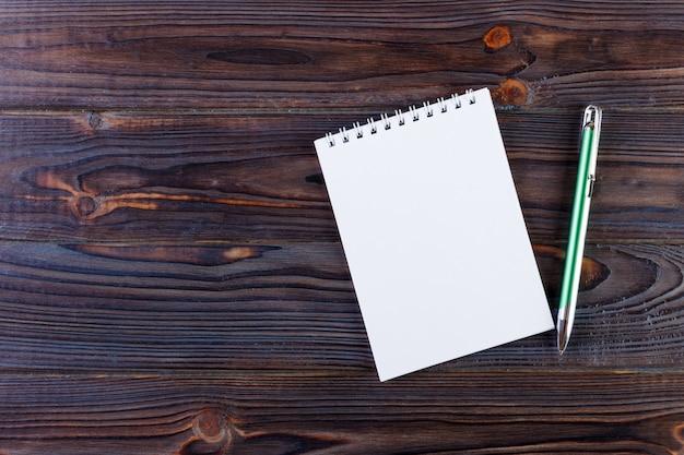 Stift und notizblock auf dem hölzernen schreibtisch Premium Fotos