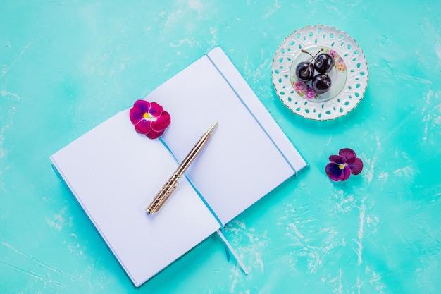Stift und offenes leeres notizbuch verspotten auf der blauen wand, die mit kirschbeere verziert wird. kopieren sie space.concept von neuen ideen, aufgabenliste, kreativem text, zielen, zielen. Premium Fotos