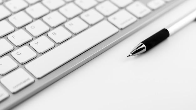 Stift und tastatur auf weißem schreibtischhintergrund. Premium Fotos