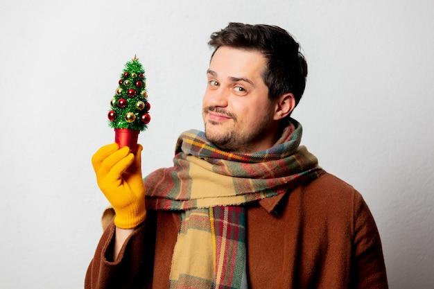 Stil mann in mantel und schal mit weihnachtsbaum Premium Fotos