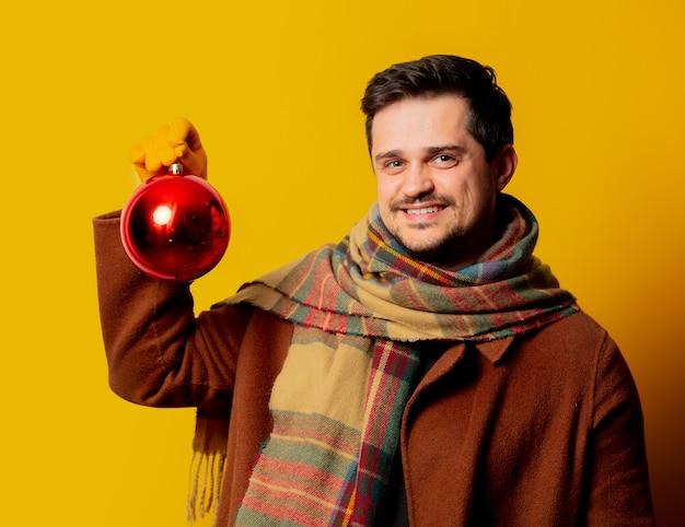 Stil mann in mantel und schal mit weihnachtskugel Premium Fotos