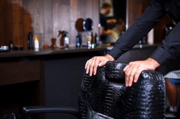 Stilist, der auf friseursalonlederstuhl sich lehnt Kostenlose Fotos