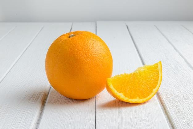 Stillleben-halber halbmond, volle frische orange frucht auf weinlese-weißer hölzerner tabelle Premium Fotos