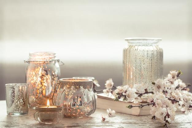 Stillleben. home gemütliche schöne einrichtung im wohnzimmer, eine vase mit frühlingsblumen und kerzen auf einem hölzernen hintergrund, das konzept der innendetails Kostenlose Fotos