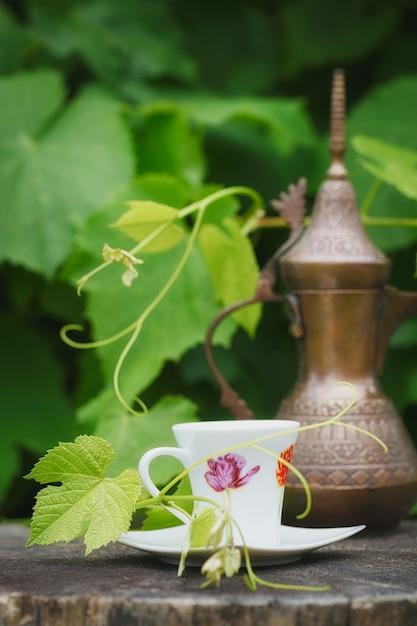 Stillleben mit antikem krug und tasse kaffee mit grünen pflanzen bedeckt Premium Fotos