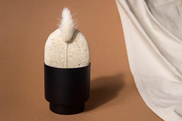 Stillleben mit blume, stein, stoff und schwarzer vase auf strukturiertem wandhintergrund im wabi-sabi-stil. selektive fokus-seitenansicht Premium Fotos