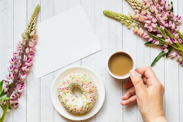 Stillleben mit einem tasse kaffee- und lupinenblumenkrapfen notizblock auf einem hellen holztisch. platz kopieren Premium Fotos