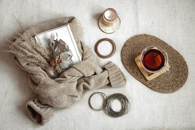 Stillleben mit frauenarmbändern, einer tasse tee auf einem korbständer, einer kerze und einem warmen pullover, herbstkomfortkonzept draufsicht Kostenlose Fotos