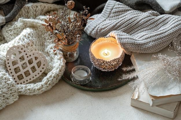 Stillleben mit kerzen in kerzenhaltern, dekordetails und strickwaren. Kostenlose Fotos