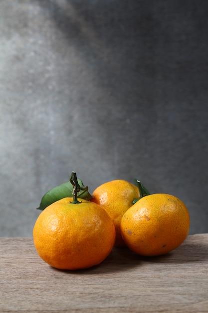 Stillleben mit mandarinen auf holztisch mit grunge-platz Premium Fotos
