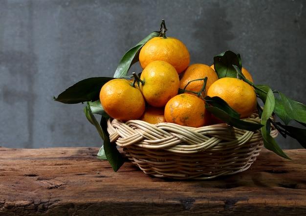 Stillleben mit mandarinen im korb auf holztisch mit grunge-platz Premium Fotos