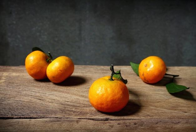 Stillleben mit orangefarbenen früchten auf holztisch mit grunge-platz Premium Fotos