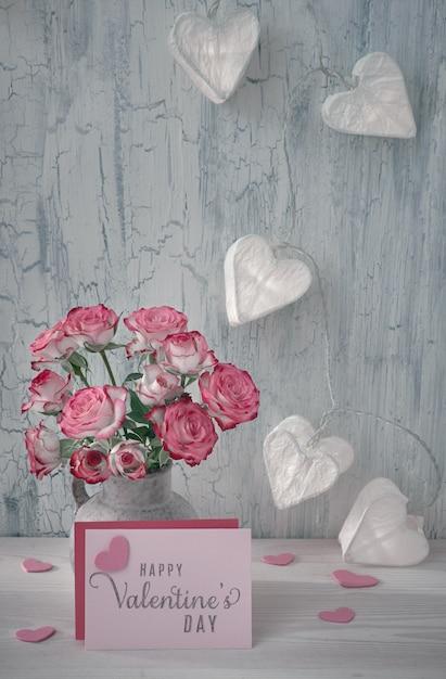 Stillleben zum valentinstag mit leerer papierkarte, rosa rosen und girlandenlichtern in form von papierherzen auf rustikalem hintergrund Premium Fotos