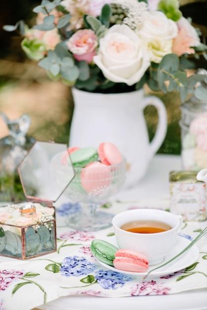 Stilllebenbrautmorgen, teller mit tasse tee, champagnerglas, eheringen und blumenblumenstrauß Premium Fotos