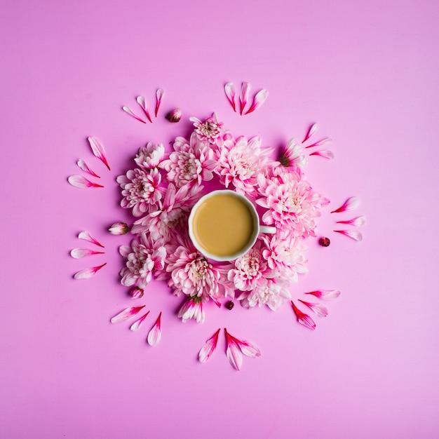 Stilllebenfoto-draufsicht von kaffee mit milch in einer tasse mit chrysanthemenblumen um ihn herum Premium Fotos