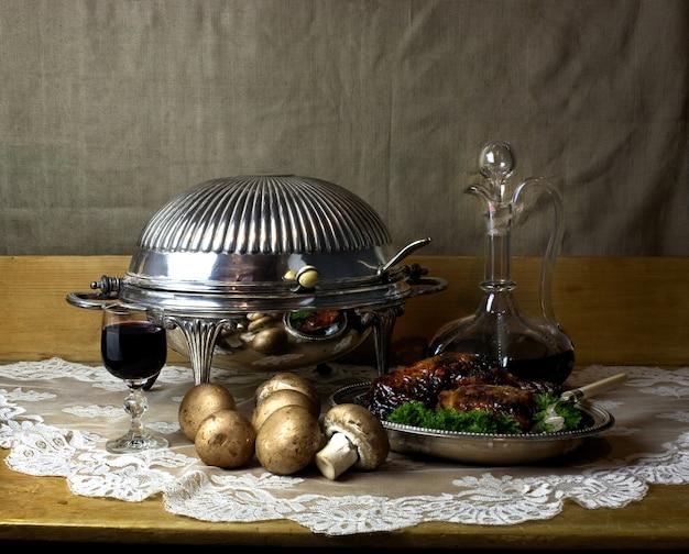 Stilllebenfoto von karaffe und glas portwein, antikem chafing dish, pilzen und brathähnchen Kostenlose Fotos