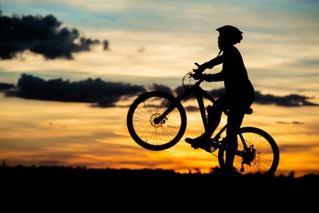Stillstehendes schattenbild des radfahrers bei sonnenuntergang. aktives outdoor-sportkonzept Kostenlose Fotos