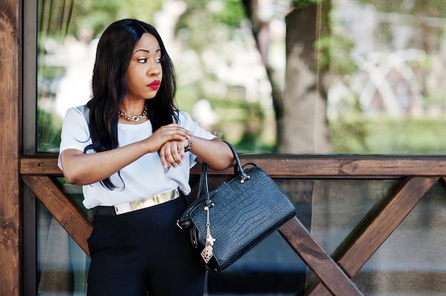 Stilvolle afroamerikanergeschäftsfrau mit handtasche auf straßen der stadt und betrachten von uhren. Premium Fotos