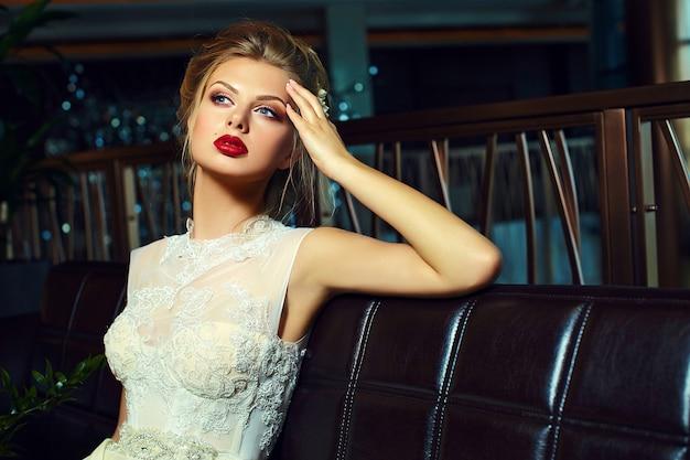 Stilvolle blonde braut des zaubers mit hellem make-up und mit den roten lippen Kostenlose Fotos