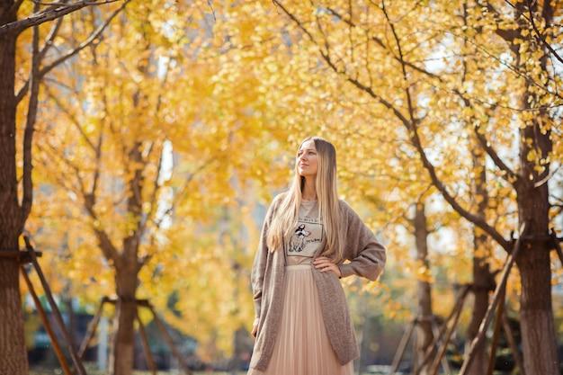 Stilvolle blonde frau im herbstlichen park Premium Fotos