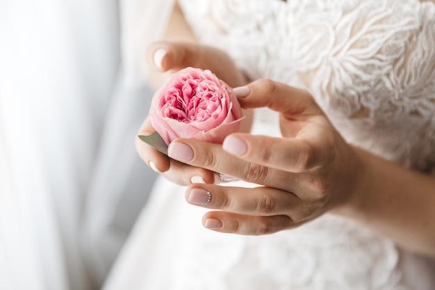 Stilvolle braut hält eine rose Kostenlose Fotos