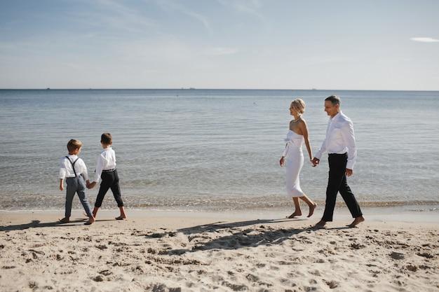 Stilvolle familie geht am strand in der nähe des ruhigen meeres spazieren, eltern und kinder halten sich an den händen Kostenlose Fotos