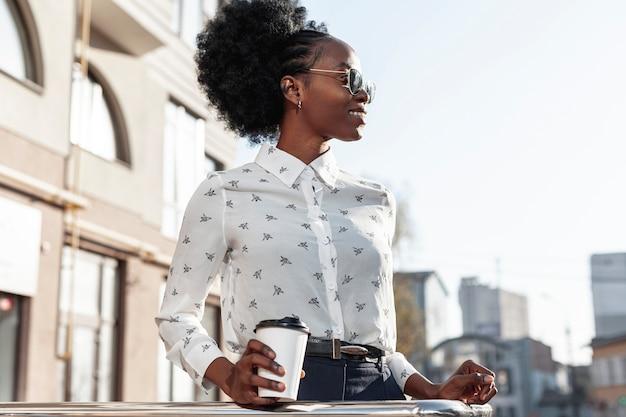 Stilvolle frau des niedrigen winkels mit kaffee auf balkon Kostenlose Fotos