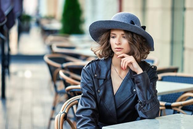 Stilvolle frau, die altmodischen mantel trägt, pause im straßenaußencafé hat Premium Fotos