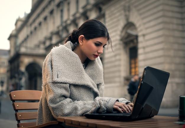 Stilvolle frau, die an einem laptop arbeitet Premium Fotos