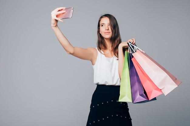 Stilvolle frau, die selfie mit einkaufstüten auf weißem hintergrund mit papiertüten in ihren armen macht Kostenlose Fotos