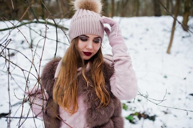 Stilvolle frau im pelzmantel und im headwear am winterwald. Premium Fotos