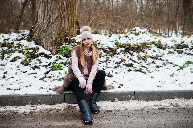 Stilvolle frau im pelzmantel und in der kopfbedeckung am wintertag auf sitzendem rand ofroad. Premium Fotos