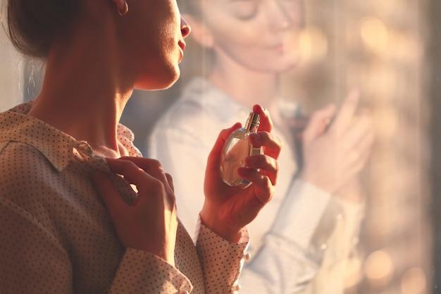 Stilvolle frau in der bluse, die eine flasche lieblingsparfüm bei sonnenuntergang sprüht. Premium Fotos
