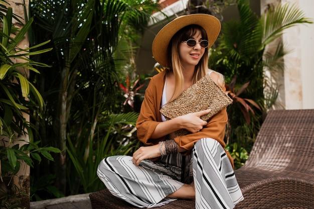 Stilvolle frau in sommerkleidung, die sich im hotel entspannt und trendige sonnenbrillen, strohhut und handtasche, böhmische armbänder und accessoires genießt. Kostenlose Fotos