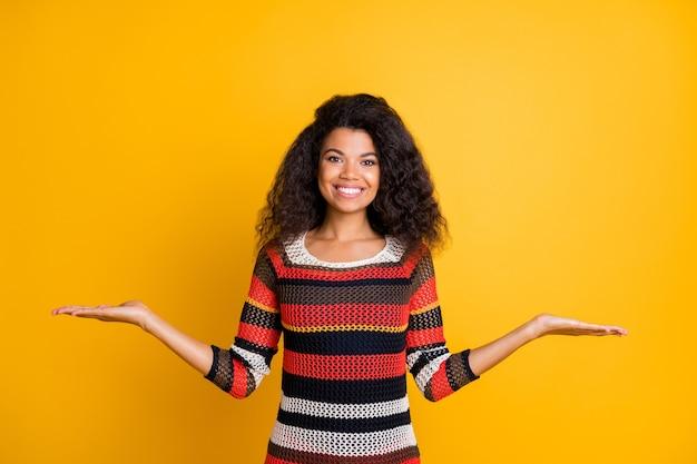 Stilvolle frau mit afro-frisur, die gegen die orange wand aufwirft Premium Fotos