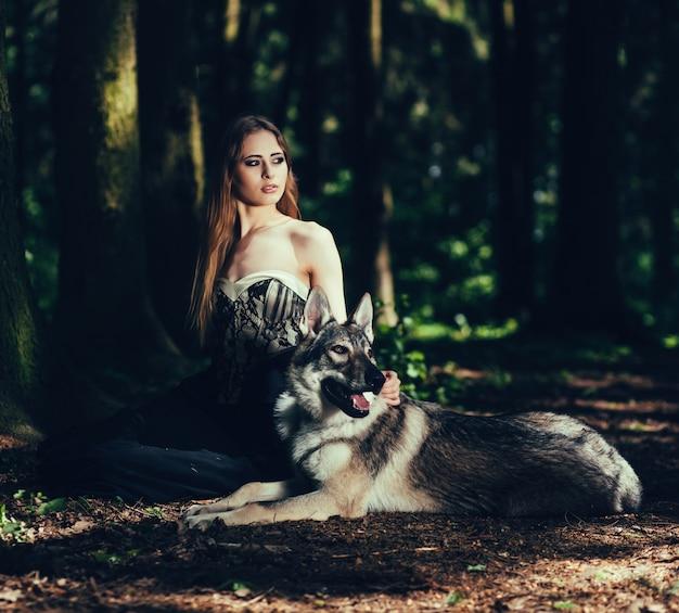 Stilvolle frau mit einem hund im wald Premium Fotos