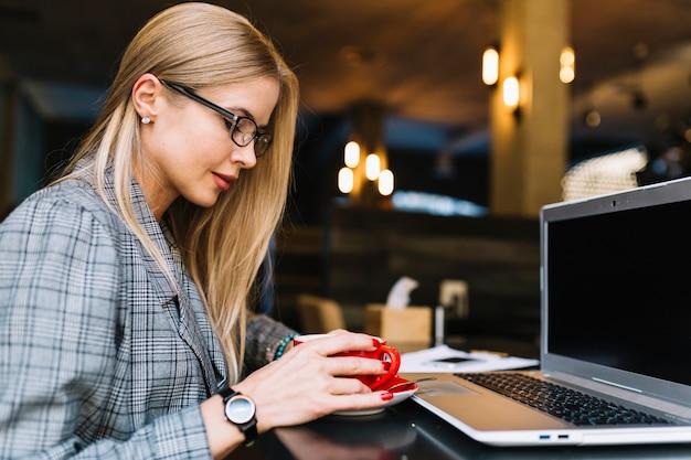 Stilvolle geschäftsfrau mit laptop in der gemütlichen kaffeestube Kostenlose Fotos