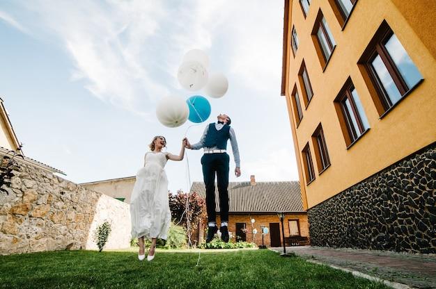 Stilvolle glückliche braut und bräutigam halten luftballons in den händen und springen Premium Fotos