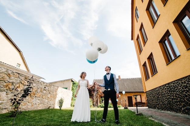Stilvolle glückliche braut und bräutigam halten luftballons in den händen. Premium Fotos